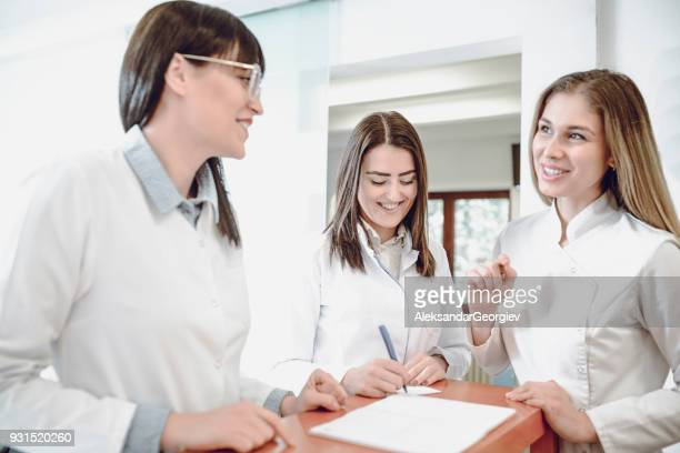 group of smiling young female doctors talking at the reception in clinic - medical receptionist uniforms stock photos and pictures