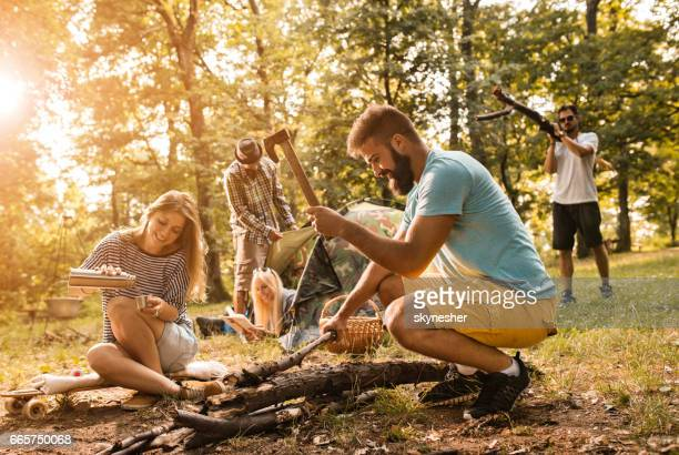 Group of smiling young people camping in the forest.