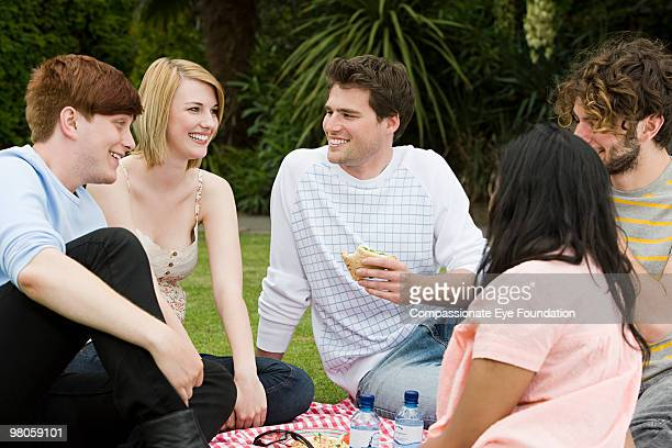 """a group of smiling young people having a picnic - """"compassionate eye"""" stock pictures, royalty-free photos & images"""
