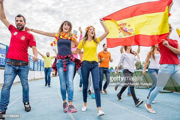 Group of soccer fans celebrating with Spanish flag