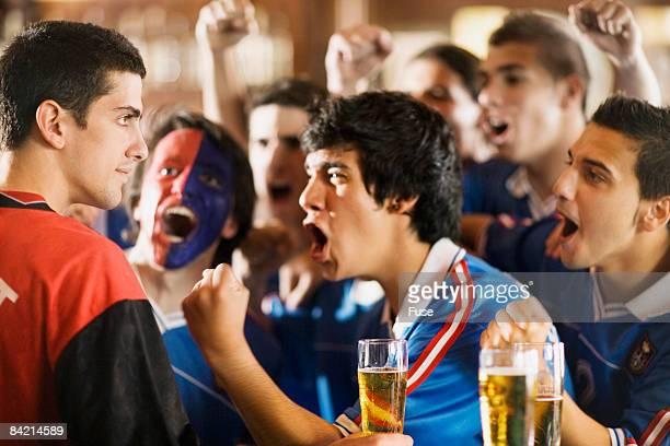 group of soccer fans cheering in bar - rivaliteit stockfoto's en -beelden