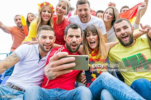 Group of soccer fans taking a selfie in stadium