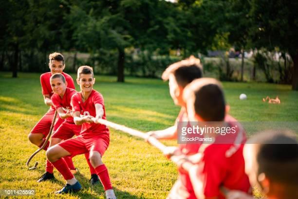 gruppe von fußball-spieler ziehen ein seil im park - jugendmannschaft stock-fotos und bilder