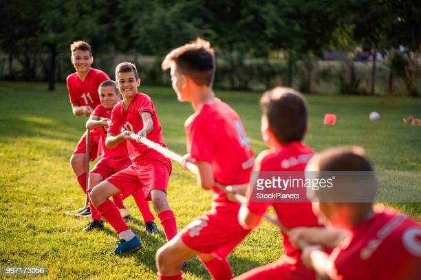 gruppe von fußball-spieler, die ein seil ziehen - jugendmannschaft stock-fotos und bilder