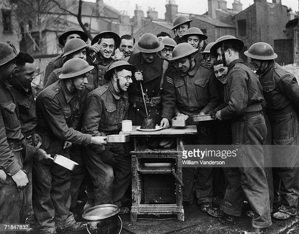 Group of soldiers from the Pioneer corp having a break from clearing London's air raid sites to have some Christmas pudding, 28th December 1940.