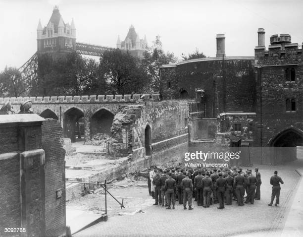 Group of soldiers inspecting bomb damage at the Tower of London.
