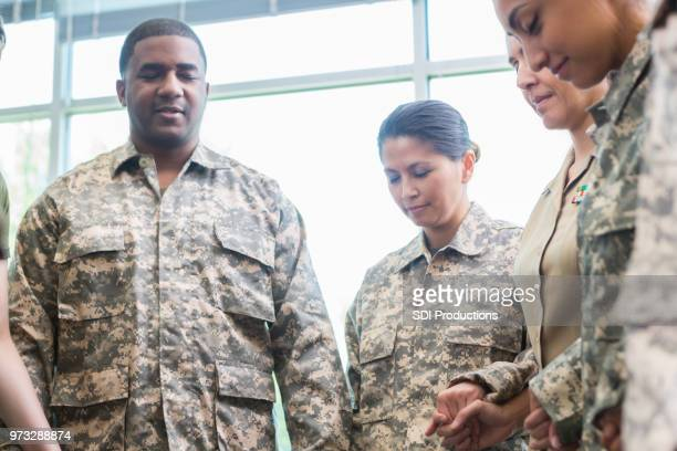 group of soldiers pray together - soldier praying stock photos and pictures