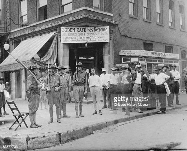 A group of soldiers stand guard with rifles and bayonets alongside a group of African American men who have gathered in front of the Ogden Cafe...