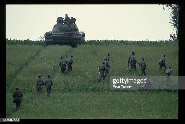 A group of soldiers walk through the grass near a military tank