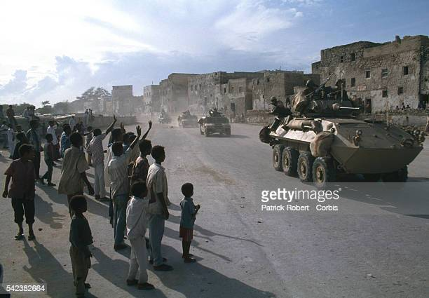 A group of Somali citizens wave to United States soldiers as the first convoy of humanitarian aid arrives in Mogadishu after 28000 United States...
