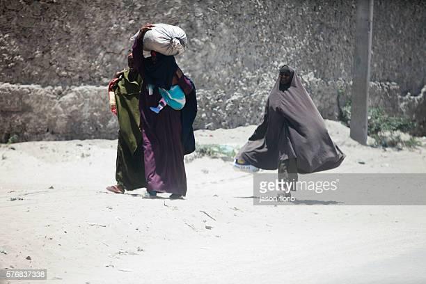 A group of Somali women wearing hijabs walk down a street in MogadishuSomalia March 2011