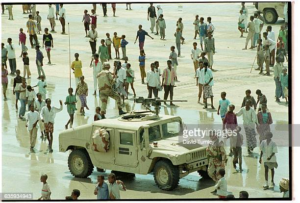 Group of Somalis gather around a US Marine humvee in an open space in Mogadishu.