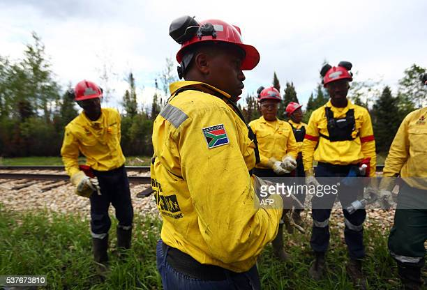 A group of South African firefighters have a break as they work to mopup hot spots in an area close to Anzac just outside of Fort McMurray Alberta on...