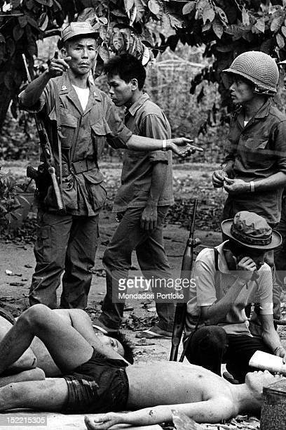 A group of South Vietnamese soldiers checking the Viet Cong captured and pulled out of a crater after the explosion of a mine Vietnam 1968