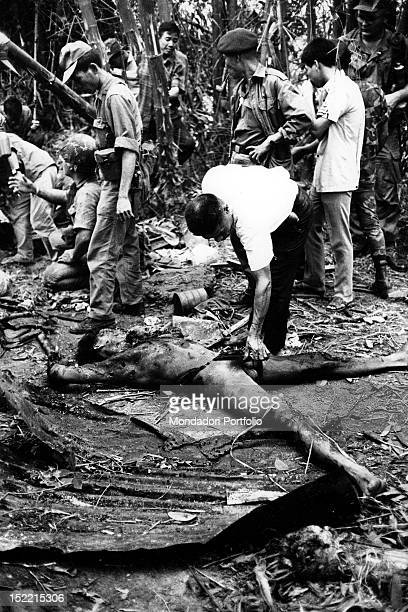 A group of South Vietnamese soldiers has found the burned body of a Viet Cong pulled out from a crater after a mine explosion Vietnam 1968