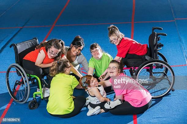 Eine Gruppe von besondere Bedürfnisse Mädchen im Fitnessraum mit Fitnesstrainer
