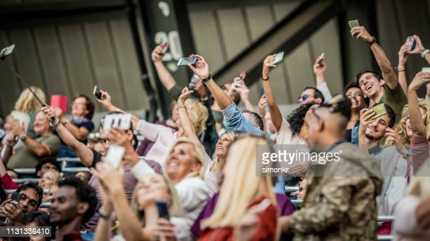 group of spectators cheering in stadium - large group of people stock pictures, royalty-free photos & images
