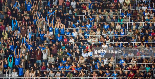 group of spectators cheering in stadium - crowd doing the wave stock pictures, royalty-free photos & images