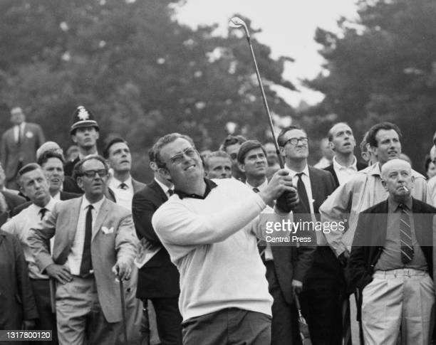 Group of spectators look on as British golfer Dave Thomas watches his iron shot off the 5th fairway during the News of the World Match Play...