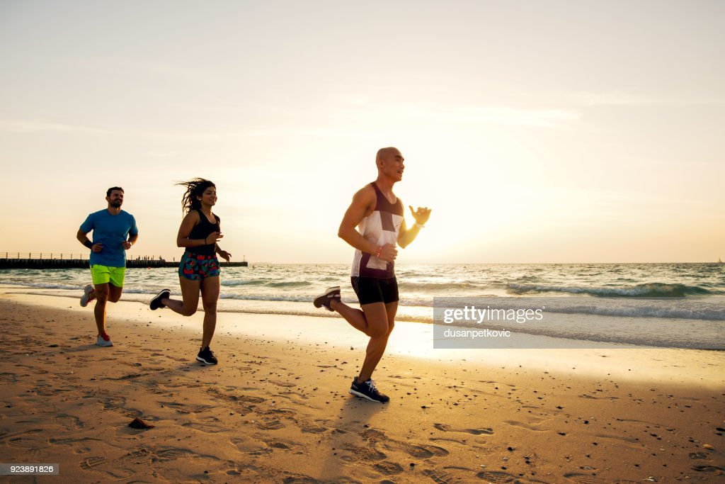 Group of sportive people running on the beach. : Stock Photo