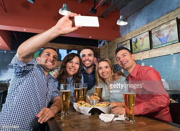 group of sports fans at a bar taking a selfie - taking a shot sport - fotografias e filmes do acervo
