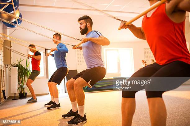 Group of sportsmen exercising on Pilates machines in health club.