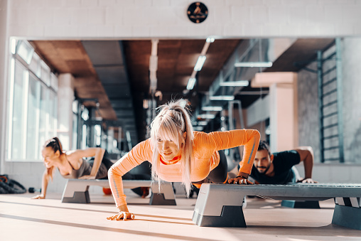 Group of sporty people doing push ups on steppers in gym. Selective focus on blonde woman, in background mirror. 1127582573