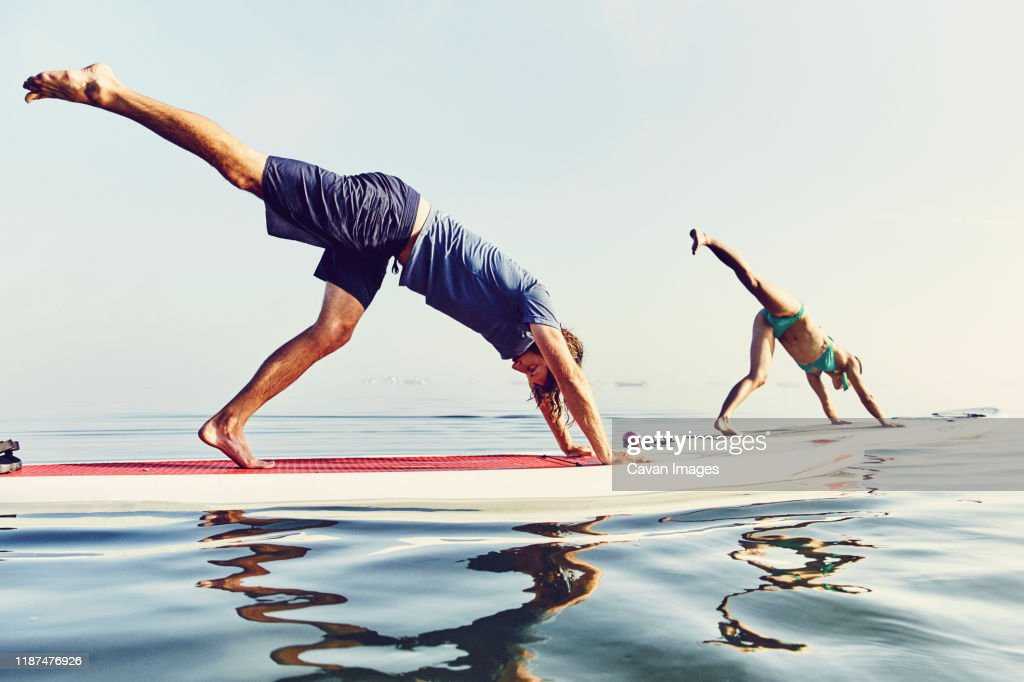 Two Women On Standup Paddle Boarders Doing Yoga At Sunrise