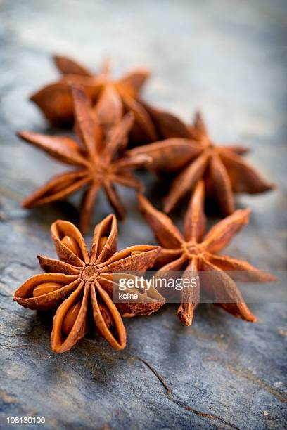 A group of star anise on a plain background