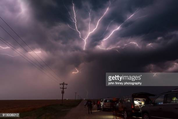 Group of storm chasers with lightning overhead