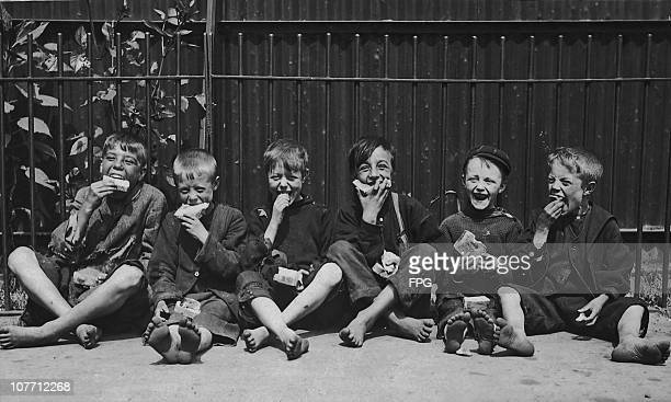 A group of street children enjoying free meal circa 1920's