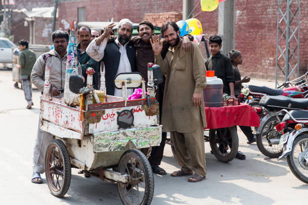 A group of street vendors are standing together in front of an ice cream rickshaw on a street on February 27 2014 in Lahore Pakistan