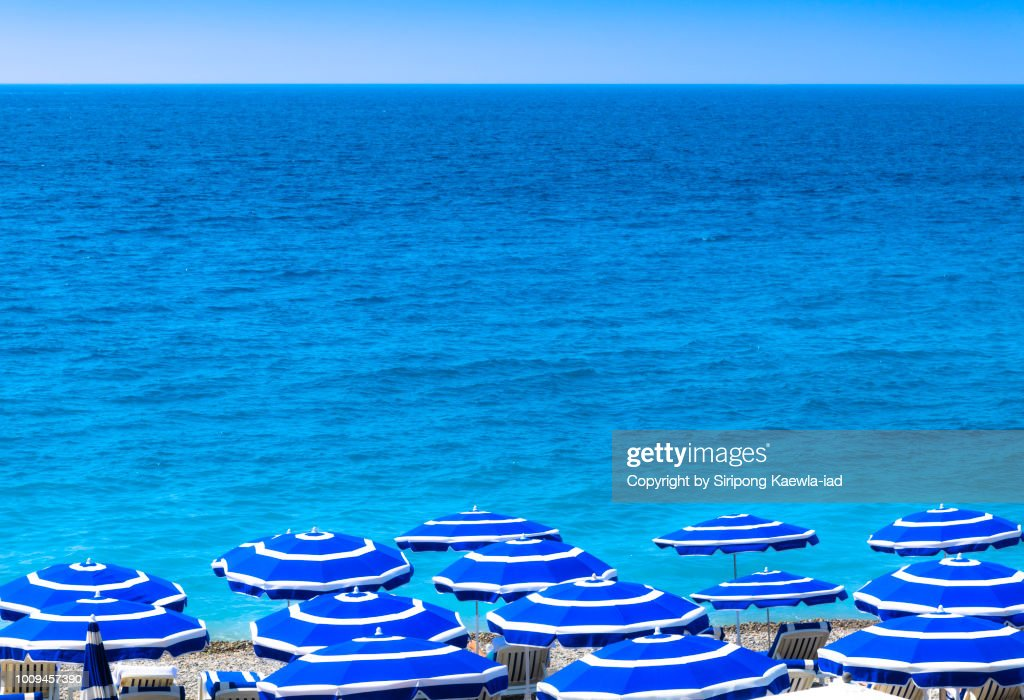 Group of striped beach umbrellas in Nice, France. : Stock Photo