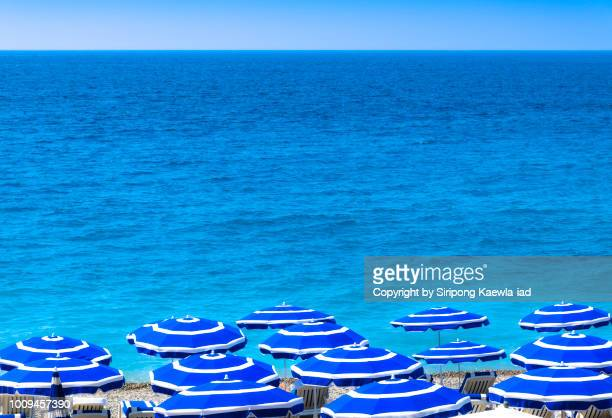 group of striped beach umbrellas in nice, france. - copyright by siripong kaewla iad stock photos and pictures