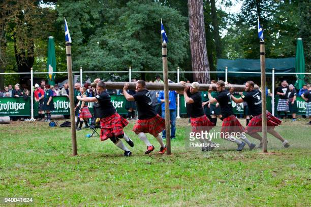 group of strong men athletes competing at scottish highland games - highland games stock pictures, royalty-free photos & images