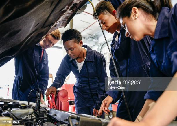 Group of student mechanics working on car engine with hood up
