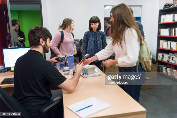 Group of students buying books in student association classroom.