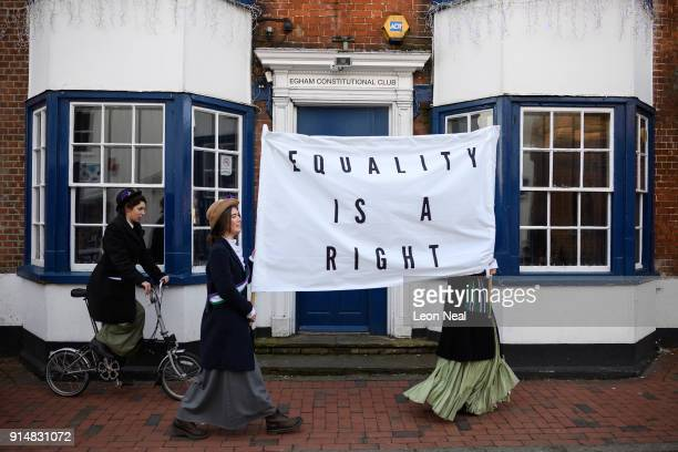 A group of students carry a banner past Egham Constitutional Club as they recreate a suffragette protest march through the town centre at Royal...