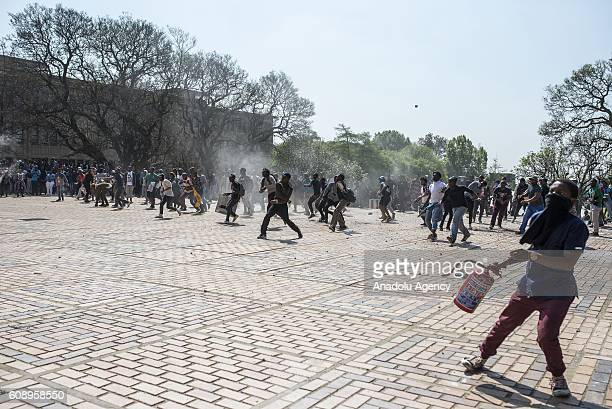 A group of students clash with security forces as they gather to protest after South African Minister of Higher Education and Training Blade...