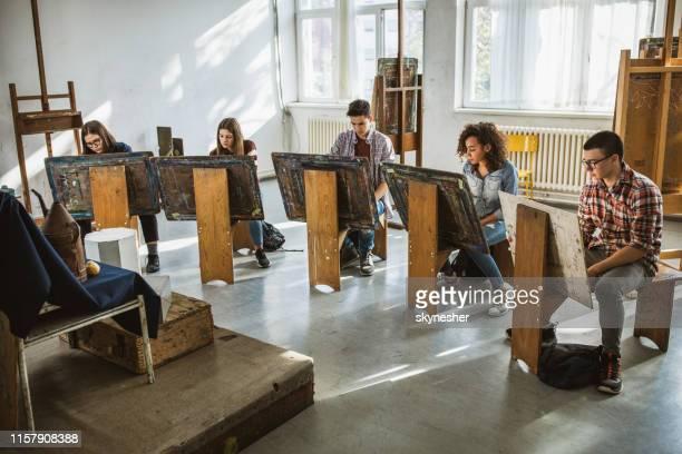 gruppe von studenten zeichnen ihre bilder auf einer klasse im kunstatelier. - aktmodel stock-fotos und bilder