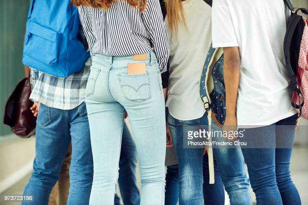 group of students dressed in jeans, cropped rear view - femme entre deux hommes photos et images de collection