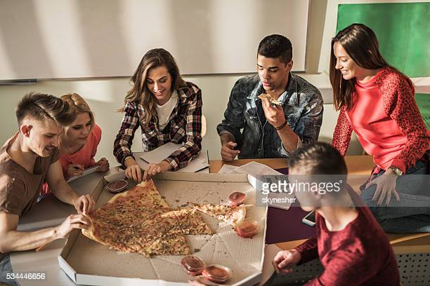 Group of students eating pizza on lunch break in classroom.