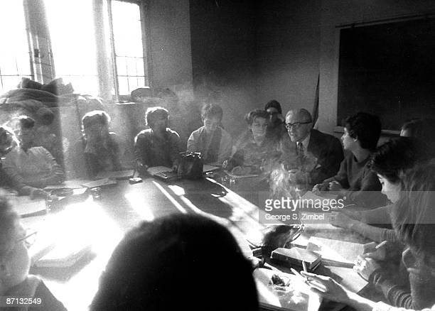 A group of students gathered around a table discussing lessons during a seminar at Sarah Lawrence College Bronxville NY 1960s