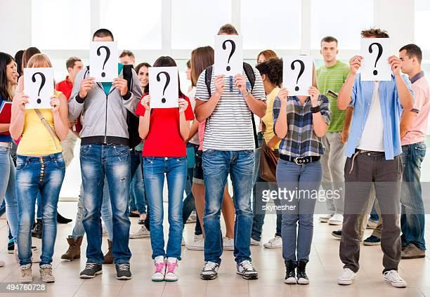 Grupo de estudiantes esconden sus rostros con signo de interrogación.