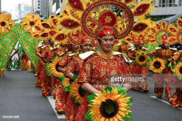 A group of students in colorful costumes line up while awaiting their turn to perform during the celebration of Makati city's 344th founding...