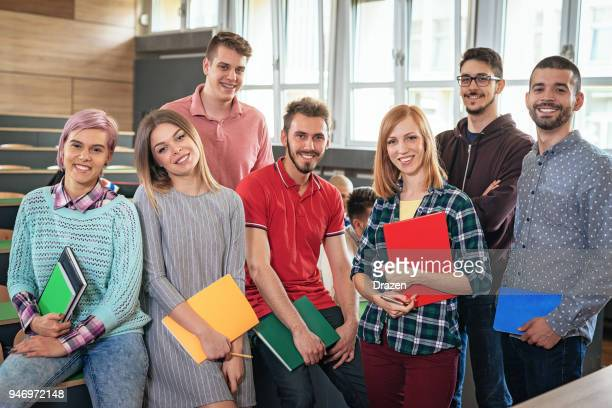 group of students in the lecture hall with notebooks - alumni stock pictures, royalty-free photos & images