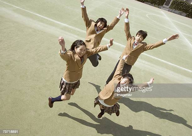 Group of students jumping in sports field