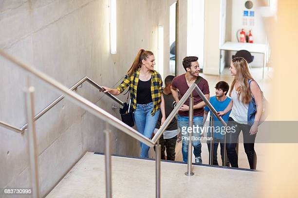 Group of students moving up stairway at higher education college
