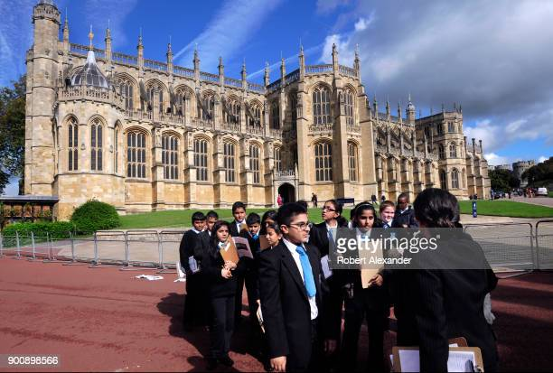 Group of students on a school field trip listen to their teacher in front of St. George's Chapel at Windsor Castle in Windsor, England. Windsor...