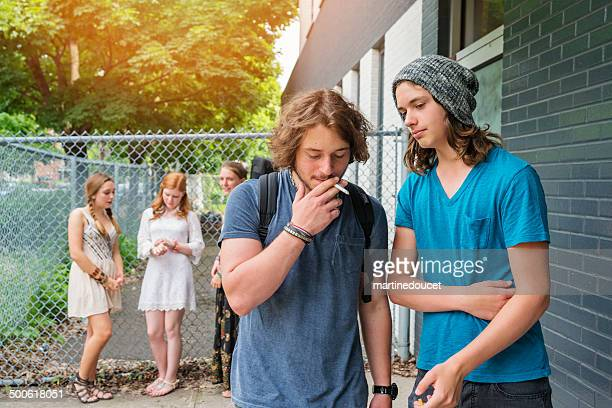 group of students outside school. boys are smoking. - smoking issues stock pictures, royalty-free photos & images